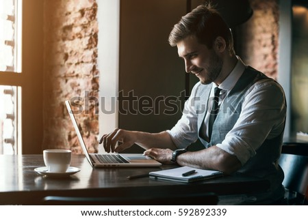 Young man drawing template for the web site associated with digital marketing, current trends and tendencies of UX / UI design. Businessman who rules his company remotely, like a freelancer.