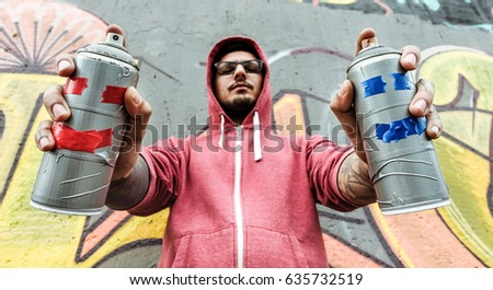 Young man drawing with two smiling sprays  - Graffiti artist painting with aerosol color cans on the wall - Rebel and against system concept - Focus on bottles spray - Unfiltered photo