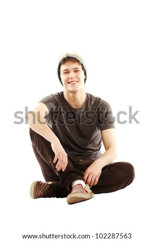 Young man dressed in hip style sitting cross legged against white background