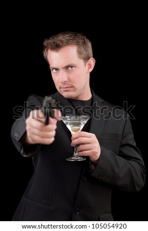 young man drinking a martini and pointing a out of focus gun