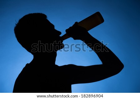 young man drinking alcohol from bottle. young drunkard holding bottle and standing