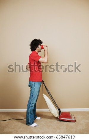 Young man drinking beer as he vacuums