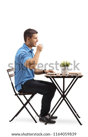 Young man drinking coffee and sitting at a table isolated on white background