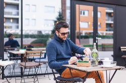 Young man drinking coffee at coffee shop garden
