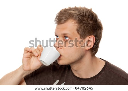 Young man drinking coffee from a coffee cup  looking away isolated on white background