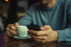 young man drinking coffee in cafe and looking at the phone screen