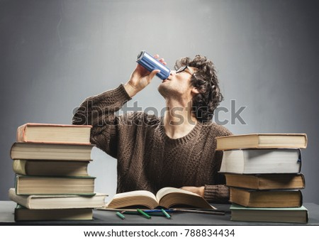 Young man drinking energy drink while studying. College student concept. Energizing before learning.