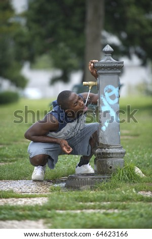 Young man drinking from a fountain