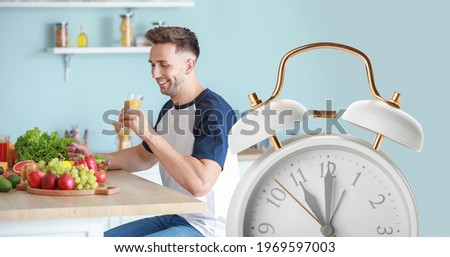 Young man drinking healthy juice and eating salad in kitchen. Time to change ストックフォト ©