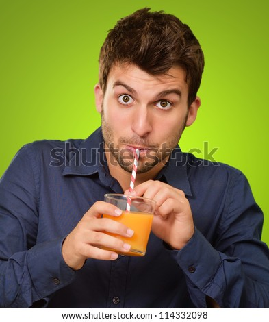 Young Man Drinking Juice On Green Background