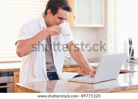 Young man drinking some coffee while working on his laptop in the kitchen