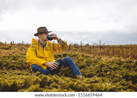young man drinking tea while sitting on the grass, close up photo. copy space, copy space