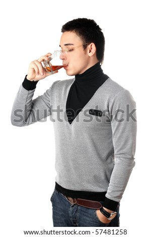 Young man drinking whiskey from a glass - stock photo