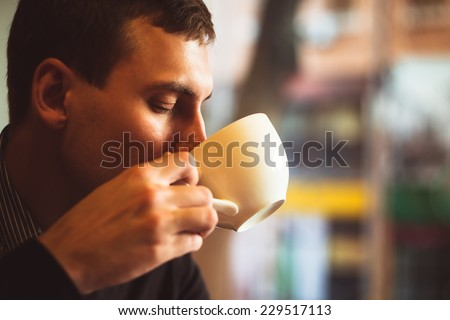 Young man drinks coffee on the street. Man drinks coffee. Young man drinks coffee outdoor. Businessman drinks coffee outdoor. Man drink coffee in cafe. Cozy atmosphere. Student drinks coffee. Coffee