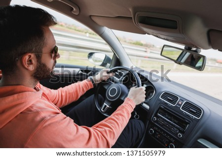Young man driving a car, interior shot #1371505979