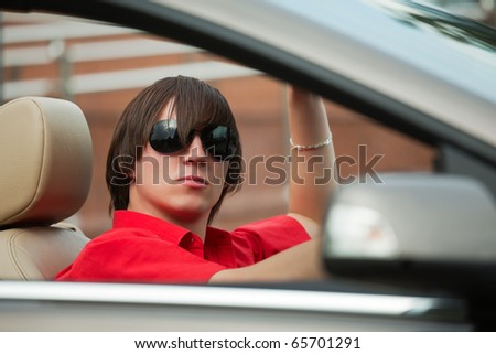 Young man driving a convertible.