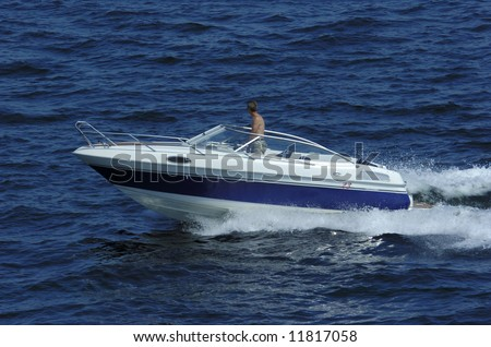 Young man driving a motor boat at ocean in the sun
