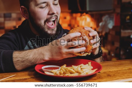 Young man eating a cheeseburger. Restaurant #556739671