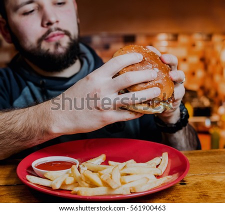 Young man eating a cheeseburger. Restaurant #561900463