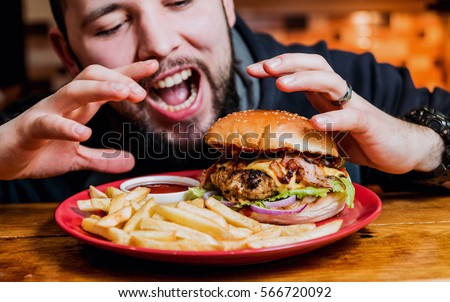 Young man eating a cheeseburger. Restaurant #566720092