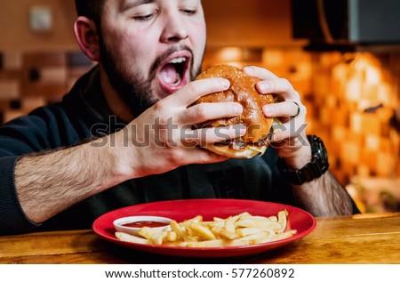 Young man eating a cheeseburger. Restaurant #577260892