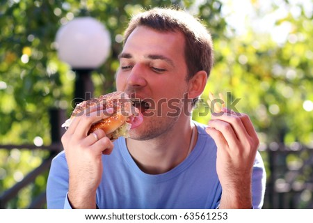 fat person eating burger. stock photo : Young man eating