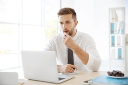 Young man eating candies while working with laptop in office
