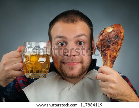 young man eating meat and drinking beer
