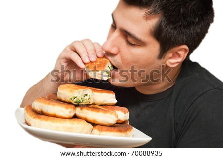 Young man eating pirojki. traditional Russian patty with eggs and onion