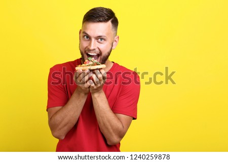 Young man eating pizza on yellow background #1240259878
