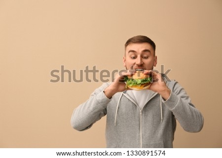 Young man eating tasty burger on color background. Space for text #1330891574