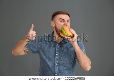 Young man eating tasty burger on grey background #1322269805