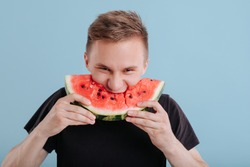 young man eats slice of watermelon, with lust, in studio, isolated on blue background, copy space