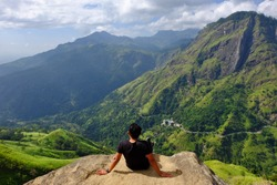 young man enjoy mountain landscape at little adam's peak, sri lanka. Back to viewer
