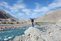 Young man enjoy sightseeing along a blue stream in Leh Ladakh India