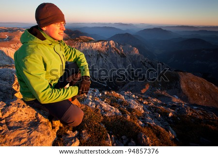 Young man enjoying autumn mountain sunset