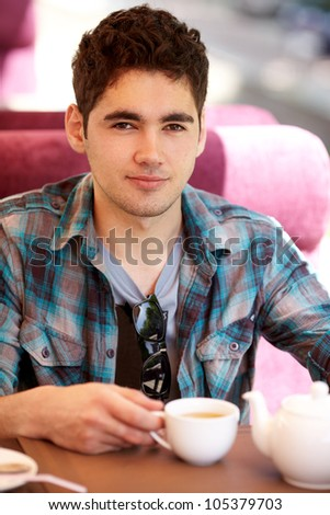 Young Man Enjoying Cup Of tea In Cafe