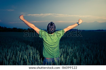 Young man enjoying his freedom/rejoicing from his success in the countryside, in a wheat field at dusk (color toned image)