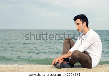 Young man enjoying his time on the beach on a sunny day, a lonely man in a yoga position