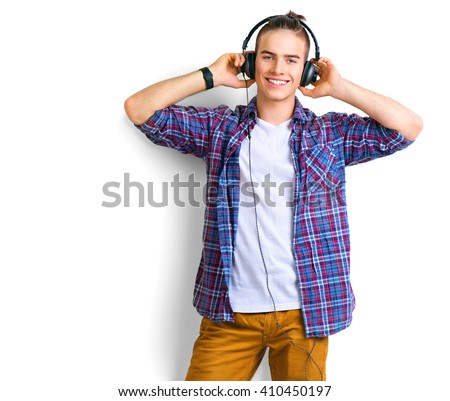 Young man enjoying music on his headphones, listening to music. Handsome young stylish man in headphones standing against white background and smiling stock photo