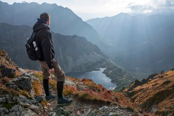 Young man enjoying the view of the Valley of Five Polish Ponds from  the top of Szpiglasowy Wierch, Tatra Mountains