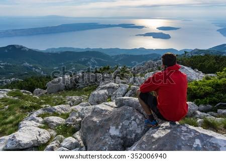 Young man enjoying view to the Adriatic sea. Velebit national park, Croatia
