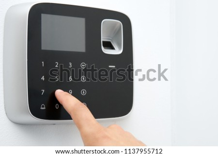 Young man entering code on alarm system keypad indoors #1137955712
