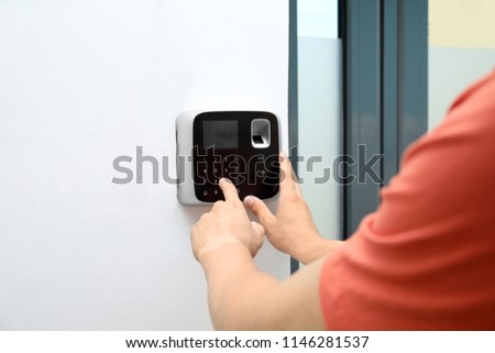 Young man entering code on alarm system keypad indoors #1146281537