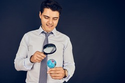 Young man examining world with magnifying glass