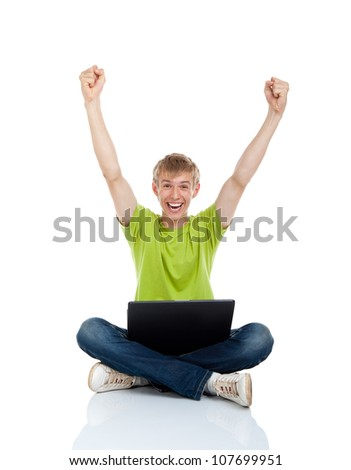 Young man excited smile sitting with laptop on floor hold hands arms up looking at camera, casual wear jeans and green shirt isolated over white background