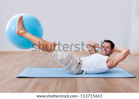 Young Man Exercising On A Pilates Ball, Indoors