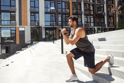 Young man exercising outside. Side view of sporty athletist down downhill exercise squat on one leg. Training outside at urban building. Hands together and concentration on exercise.