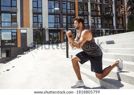 Young man exercising outside. Side view of sporty athletist down downhill exercise squat on one leg. Training outside at urban building. Hands together and concentration on exercise. Stockfoto ©