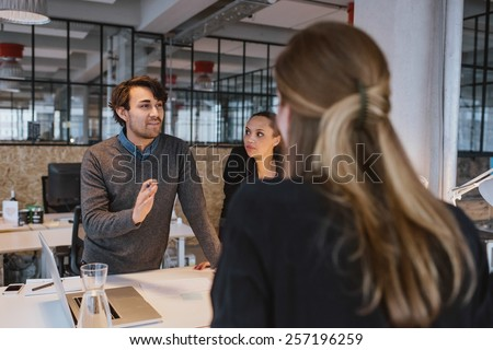 Young man explaining new business plan to coworkers during a meeting around a table in office.